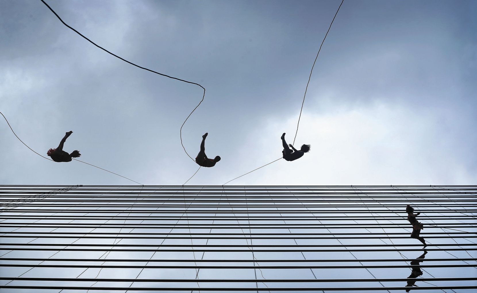 Members of the Bandaloop vertical dance company perform on the side of the KPMG Plaza office tower. The spectacle was part of a groundbreaking ceremony for Hall Arts Hotel and Residences, a 25-story downtown Dallas tower in the Arts District.
