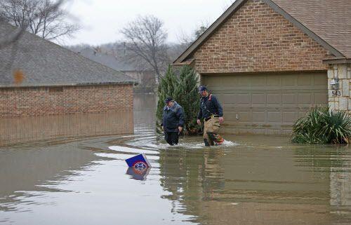 Rodger Williams (izq.) deja su inundada casa con ayuda de los bomberos de Rockwall. DMN