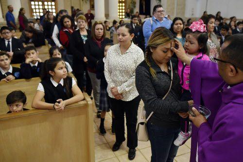 Jeanette Albarrán y su hija Sophia reciben el signo ritual en la iglesia de Santa Clara, en Dallas.