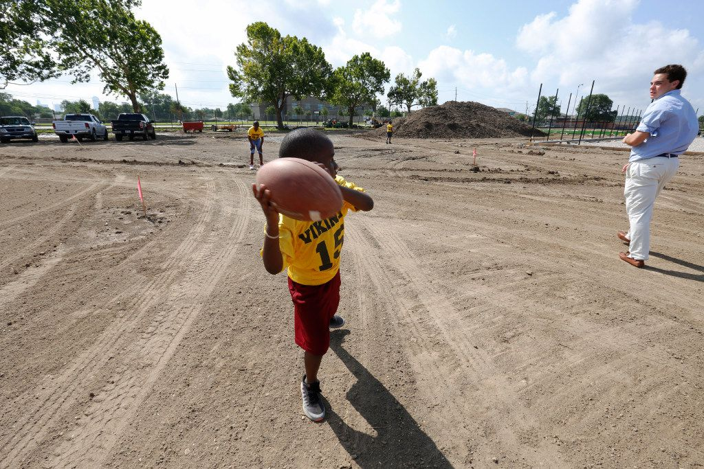 Marcus Neal, 7, in the #15 jersey with the  West Dallas Vikings, prepares to through the football to Wilson Sands, right, Mercy Street intern, after the ground breaking for  Mercy Street Football Field in West Dallas on Monday.  Neal, 7, plays football in part of the Inner League Football with Mercy Street.
