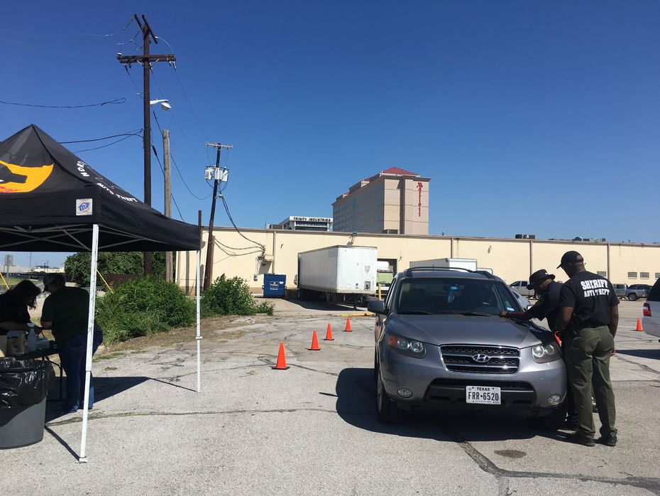 Cars wait in line to be etched in a Dallas County Health and Human Services parking lot Thursday. North Texas officials say etching a car's windows can be a deterrent to car theft.