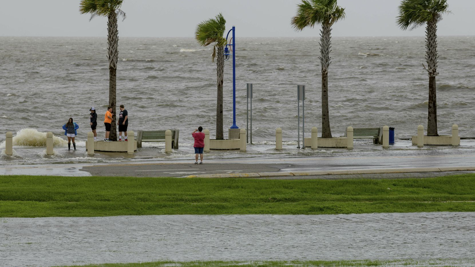 People check out the waves on Lakeshore Drive in New Orleans on Friday as water moves in from Lake Pontchartrain from Tropical Storm Barry's storm surge.
