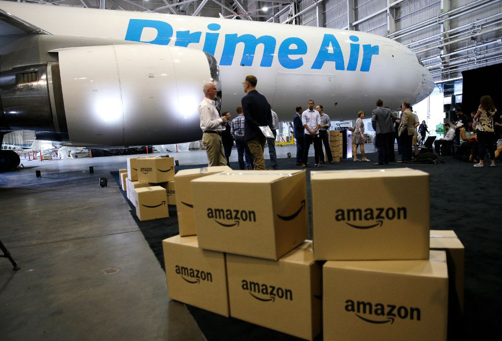 """FILE - In this Aug. 4, 2016 file photo, Amazon.com boxes are shown stacked near a Boeing 767 Amazon """"Prime Air"""" cargo plane on display in a Boeing hangar in Seattle. Buffeted by threats from Amazon drones and Uber to delivery by golf cart, the beleaguered U.S. Postal Service is counting on a different strategy to stay ahead in the increasingly competitive package business: more freedom to raise your letter prices.  (AP Photo/Ted S. Warren, File)"""