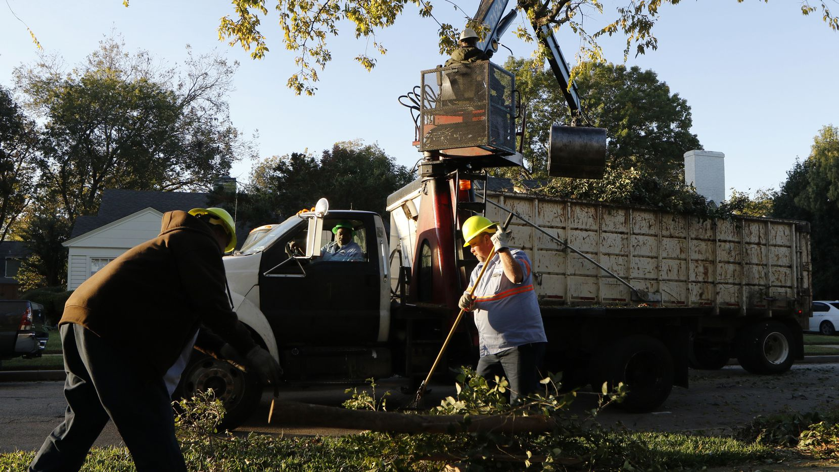 Dallas Sanitation Services employees Gustave Nealy, left, Darrell Wortham, in cab, Atmos Matthews, Rotoboom Operator, top, and Daniel Crane pick up bulk trash in the 6200 block of Revere Place in east Dallas on Monday, November 21, 2016. The City of Dallas is considering limiting its bulk trash program. Dallas collects double the amount of bulk trash of any other major Texas city and currently does not have and limitations to the amount households can leave out for pickup, but that could change.