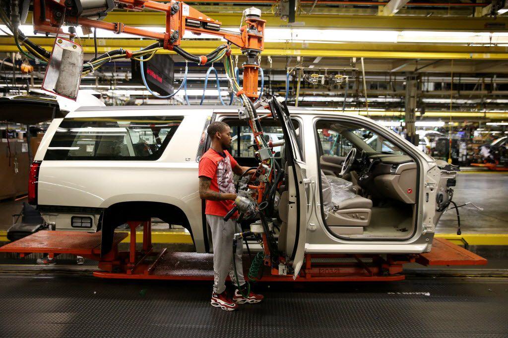 Jordan Taylor attaches a door to a Suburban being built at General Motors Assembly Plant in Arlington.