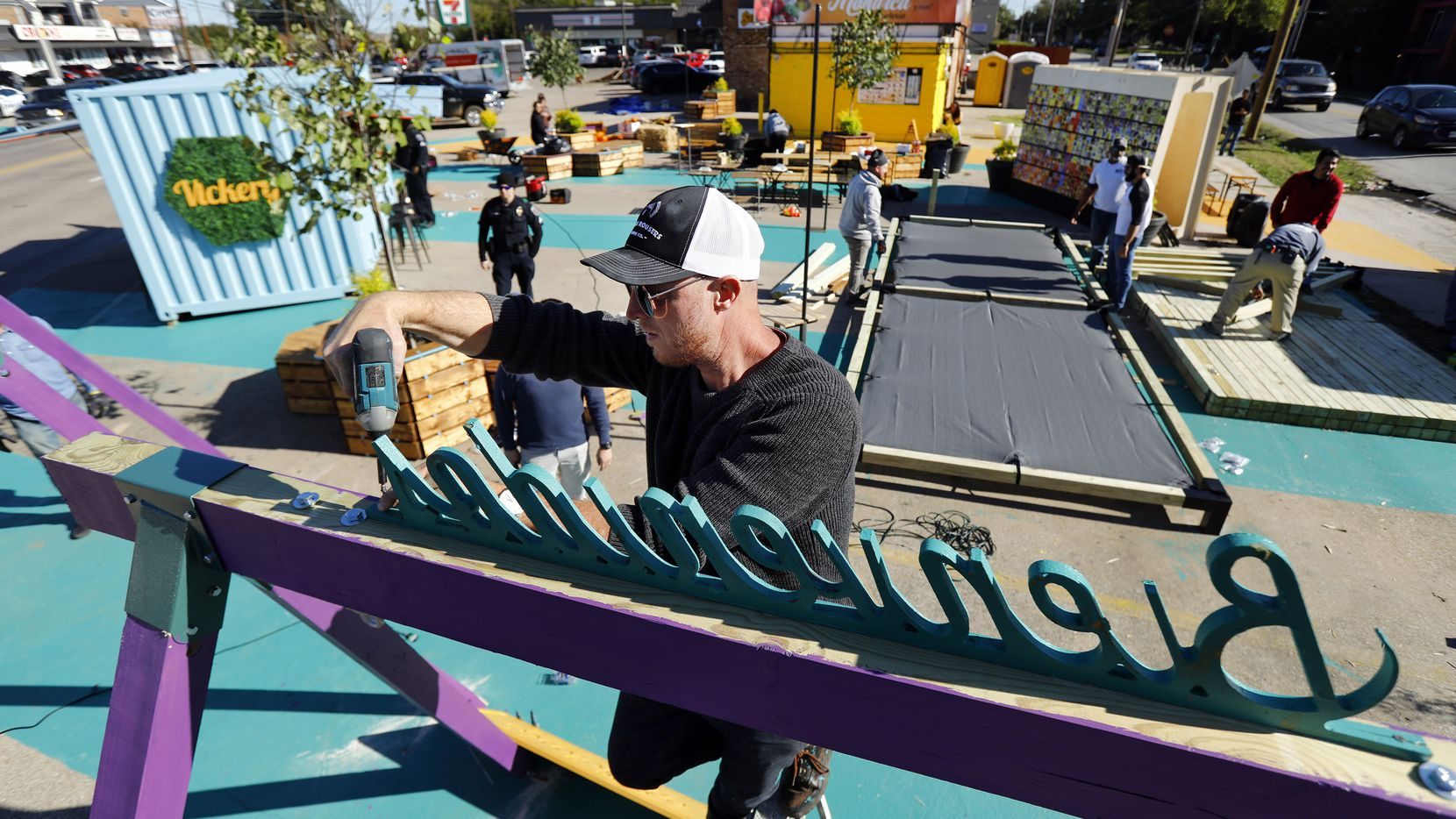 Better Block founding director Jason Roberts installs a Bienvenidos (welcome) sign atop a swing as the team makes improvements to the Five Points street intersection in the Vickery Meadow area of Dallas on Friday.Three swings welcomed kids in Spanish, Arabic and Burmese. Improvements include adding a plaza, potted trees a pop-up container store, stage, swings and colorful walkways to beautify the neighborhood. The goal is to reduce crime through improving the environment.