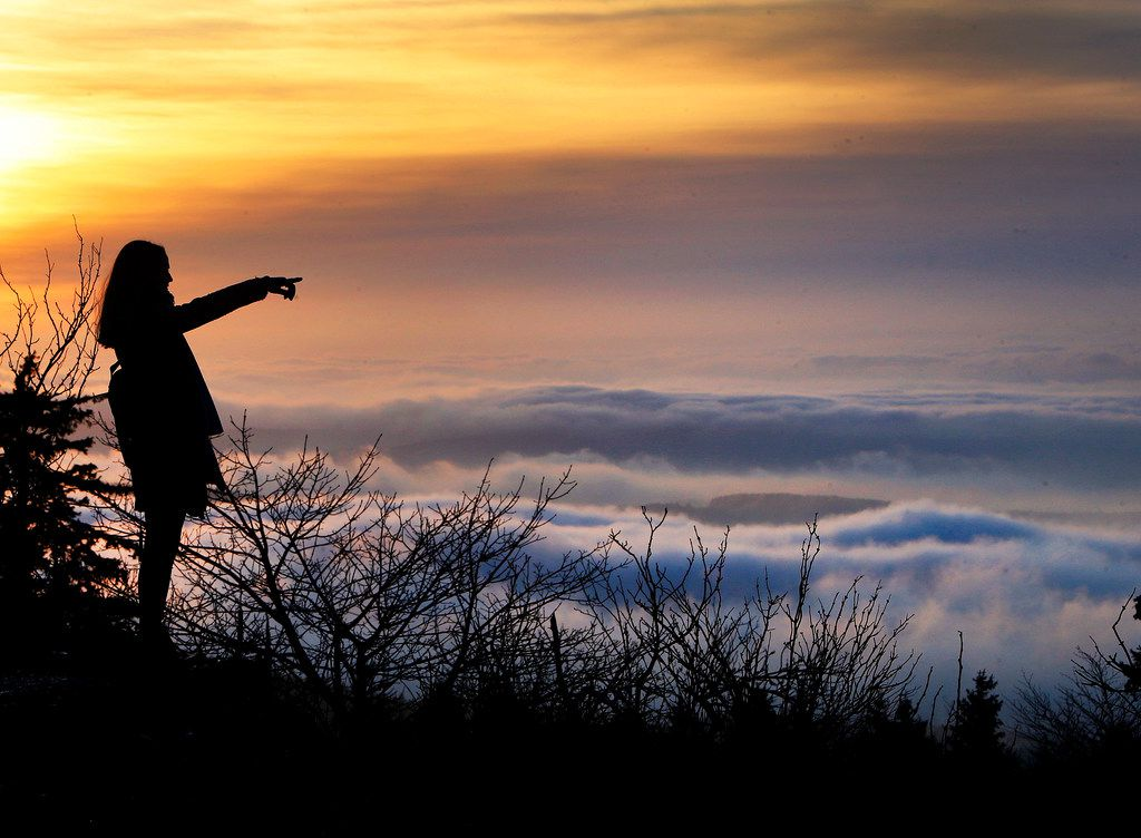A woman stands on top of the Feldberg mountain as thick fog lies over Frankfurt. (AP Photo/Michael Probst)