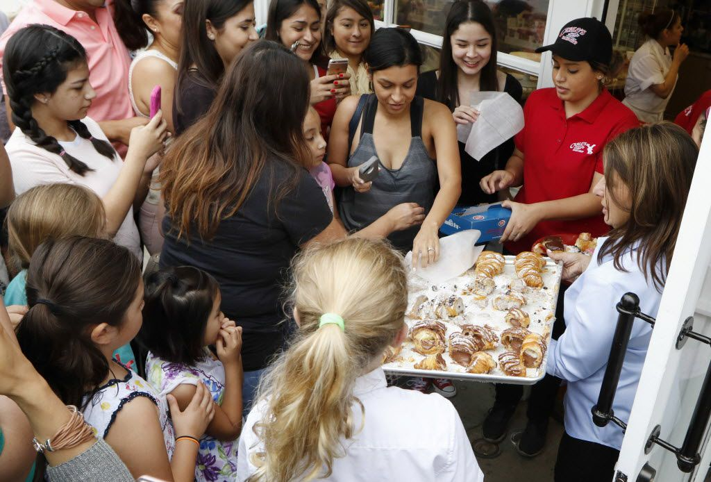 Fans of the TLC show 'Cake Boss' swarmed a Carlo's Bakery employee as they waited for opening day in Dallas.