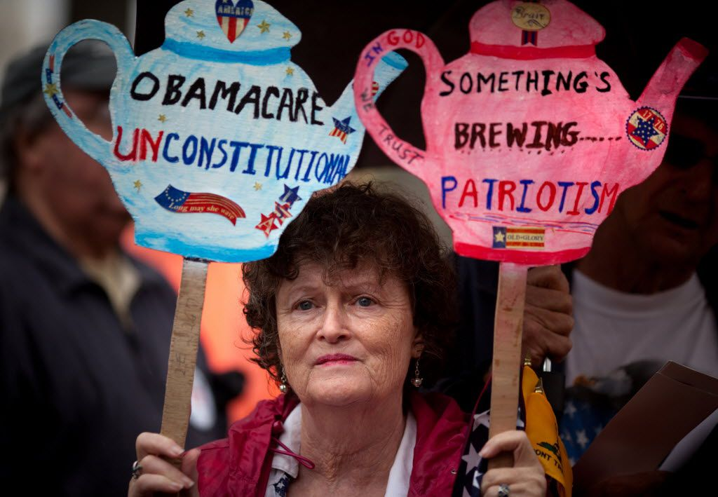 "Carlene Cahill of Petersburg, Va., holds up a set of signs she made during a tea party ""Road To Repeal Rally"" in 2012  in Washington, DC.  The group was protesting the Affordable Care Act."