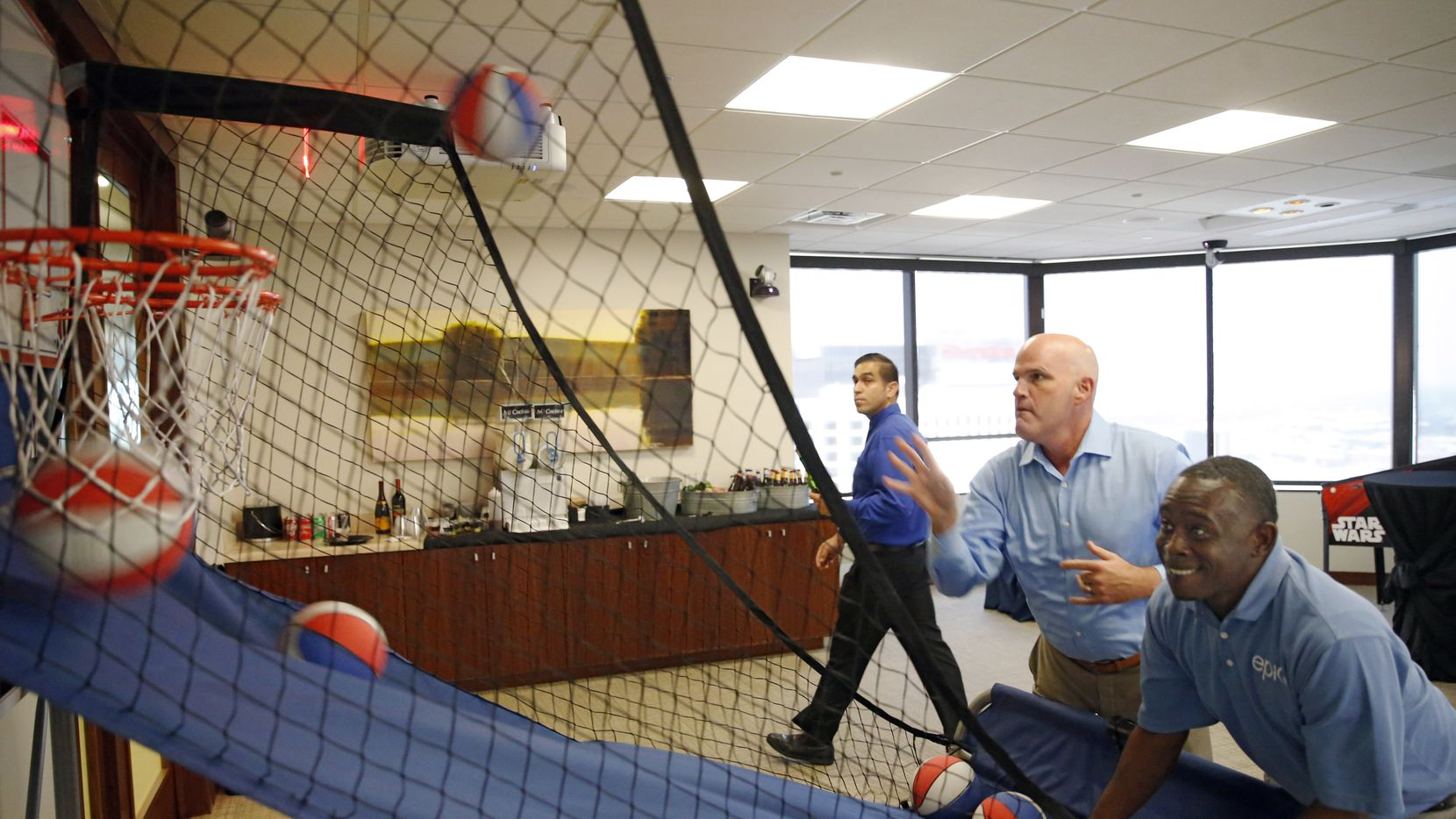 CEO Phil Appenzeller plays a game of basketball with Marcus Morgan during an employee event at Munsch Hardt Kopf & Harr in Dallas.
