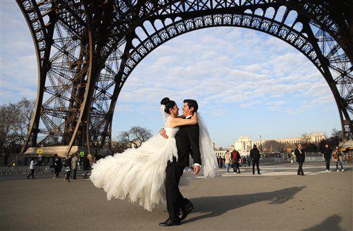 Rodrigo y Nancy de México posan para un fotógrafo bajo la Torre Eiffel durante la luna de miel de la pareja en París, el viernes 16 de diciembre de 2016. AP