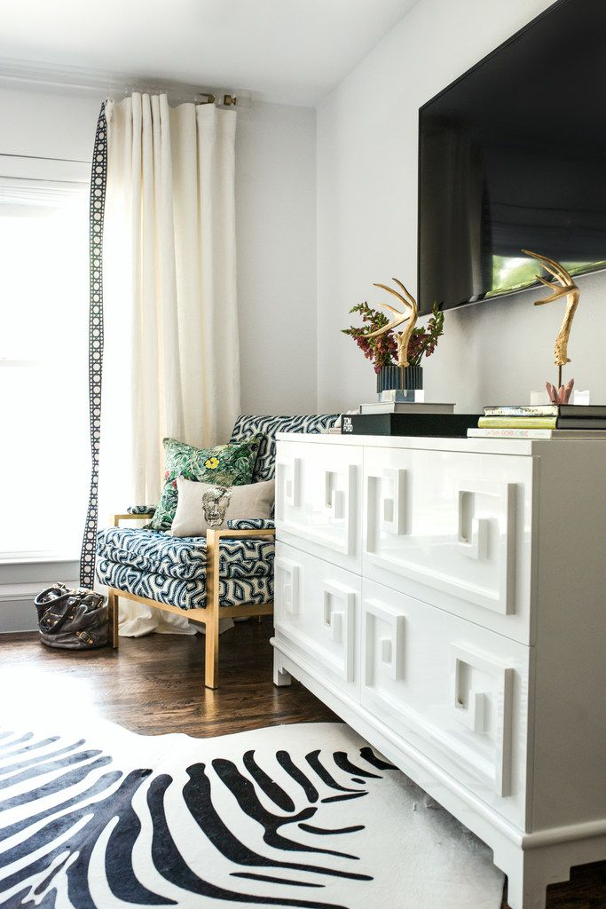 Style a television console with books, personal items and other decorative items to help balance out a television, says designer Abbe Fenimore.