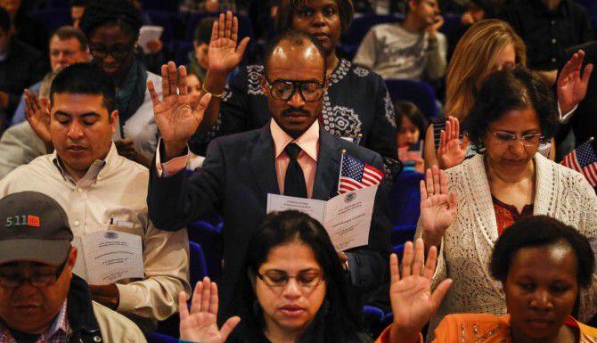 Job Bamanga (centro), originario del Congo, jura lealtad a Estados Unidos junto con otras 49 personas de 22 paises durante una ceremonia de naturalización el lunes en el Museo de Arte de Dallas. (DMN/JIM TUTTLE)