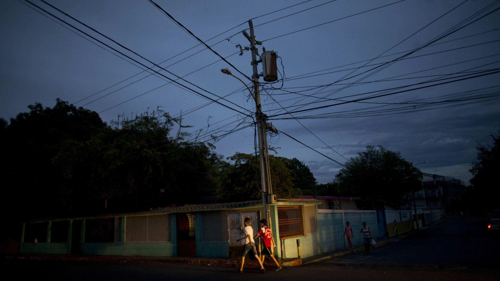 Residente de la vecindad de La Chinita, en Maracaibo, caminan en una noche oscura por la falta de luz eléctrica en varias ciudades de Venezuela.(AP)