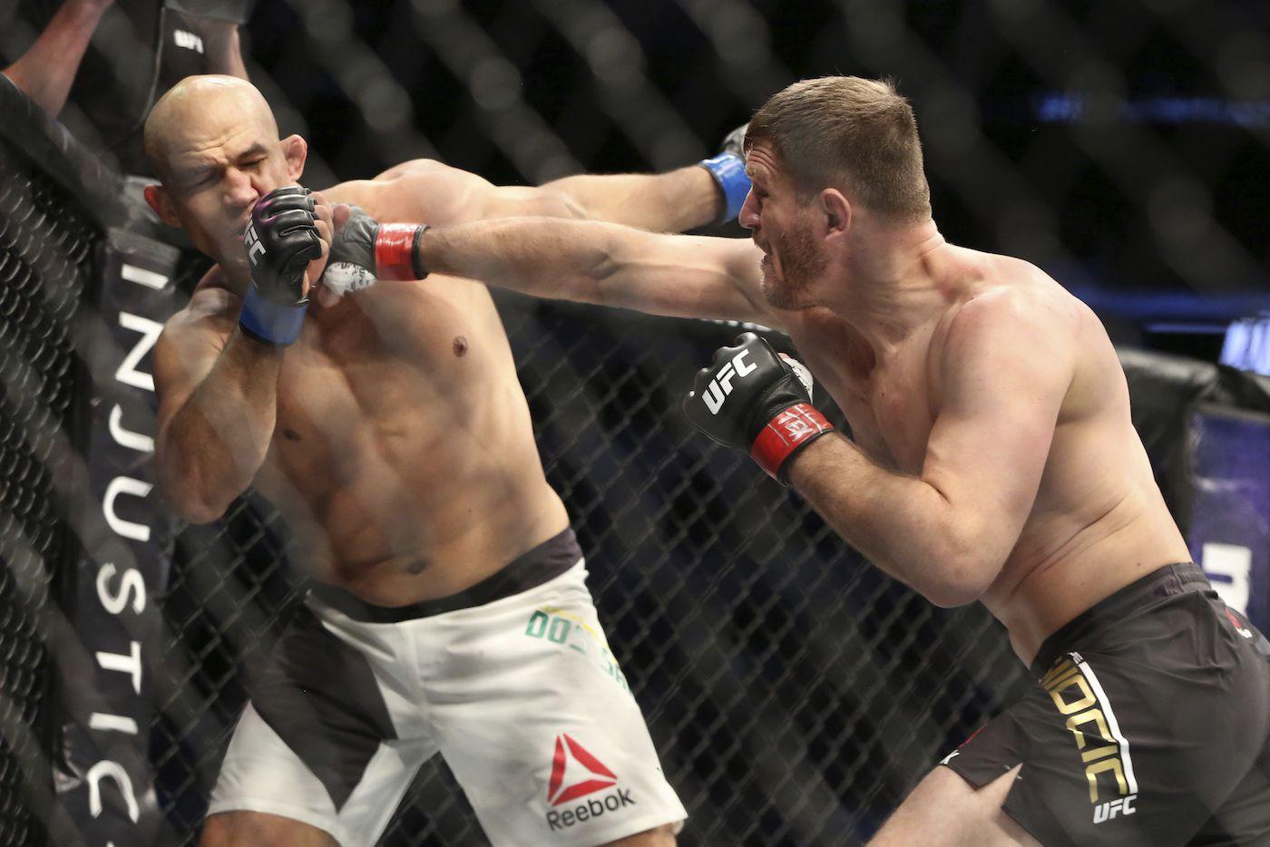 Stipe Miocic conecta un golpe en el rostro de Junior de Dos Santos, en el combate de título de peso completo de la UFC. AP