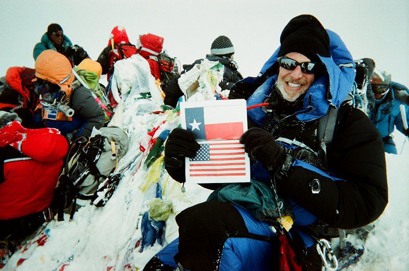 Victor Vescovo sits atop the summit of Mt. Everest holding a Texas and U.S. flag.