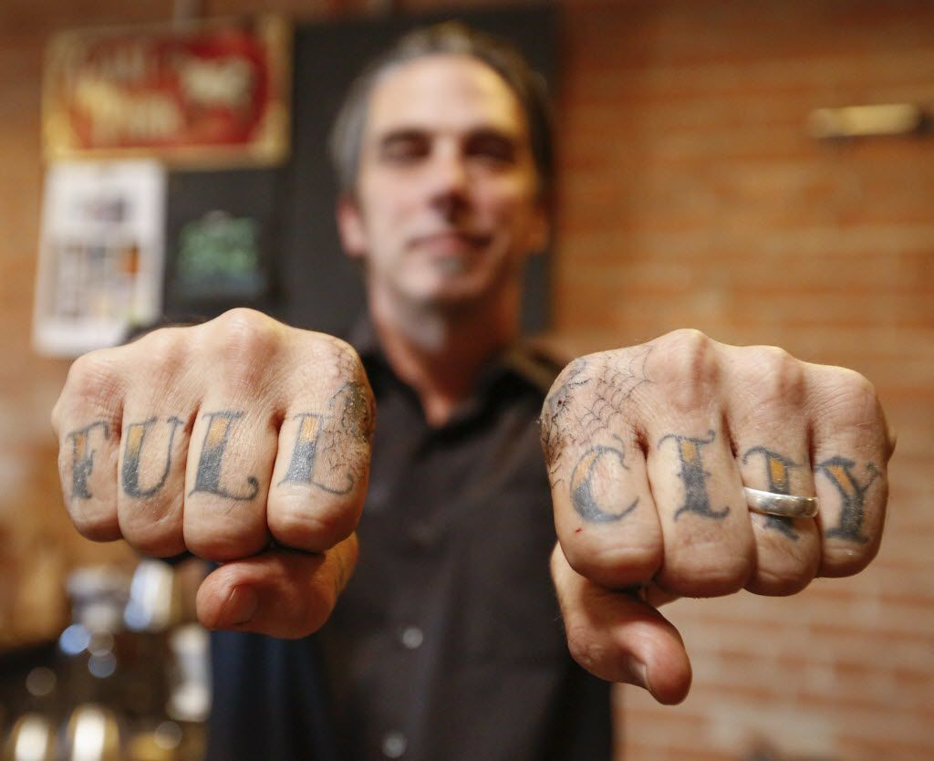 Michael Wyatt, owner the Full City Rooster has the names of his coffee roasting studio tattooed on his knuckles.