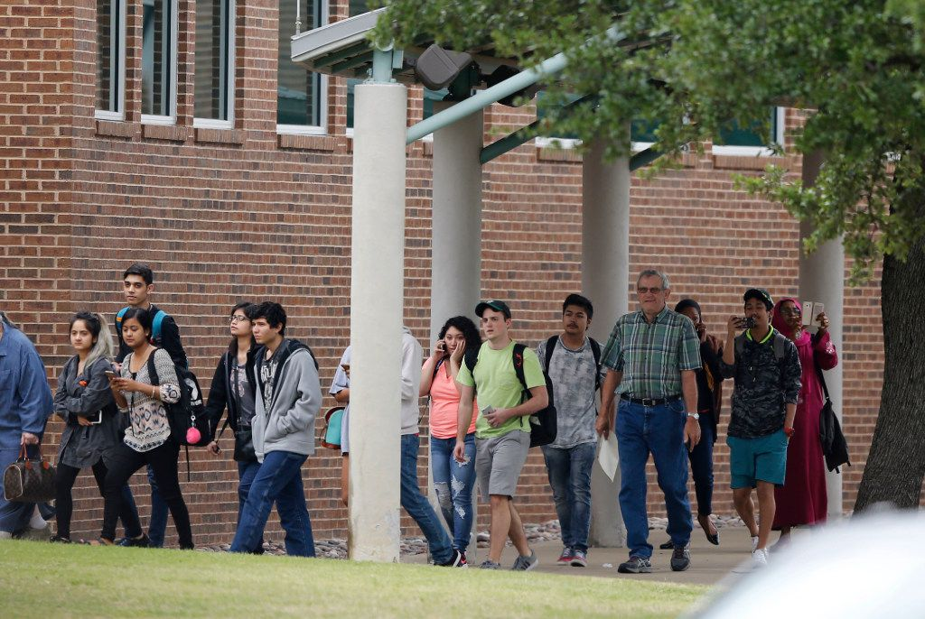 Students and faculty exit a building after a shooting at North Lake College.