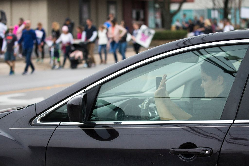 Drivers wave and honk at participants in the Dallas Women's March on Saturday.
