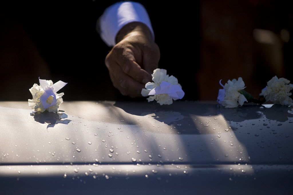 On Nov. 7, 2009, a flower is placed on a casket by a pallbearer during a funeral in St. Michaels, Ariz. Funeral costs are among the most expensive purchases we'll face but most important decisions are made emotionally rather than with a close eye on cost. (AP Photo/Gallup Independent, Cable Hoover)