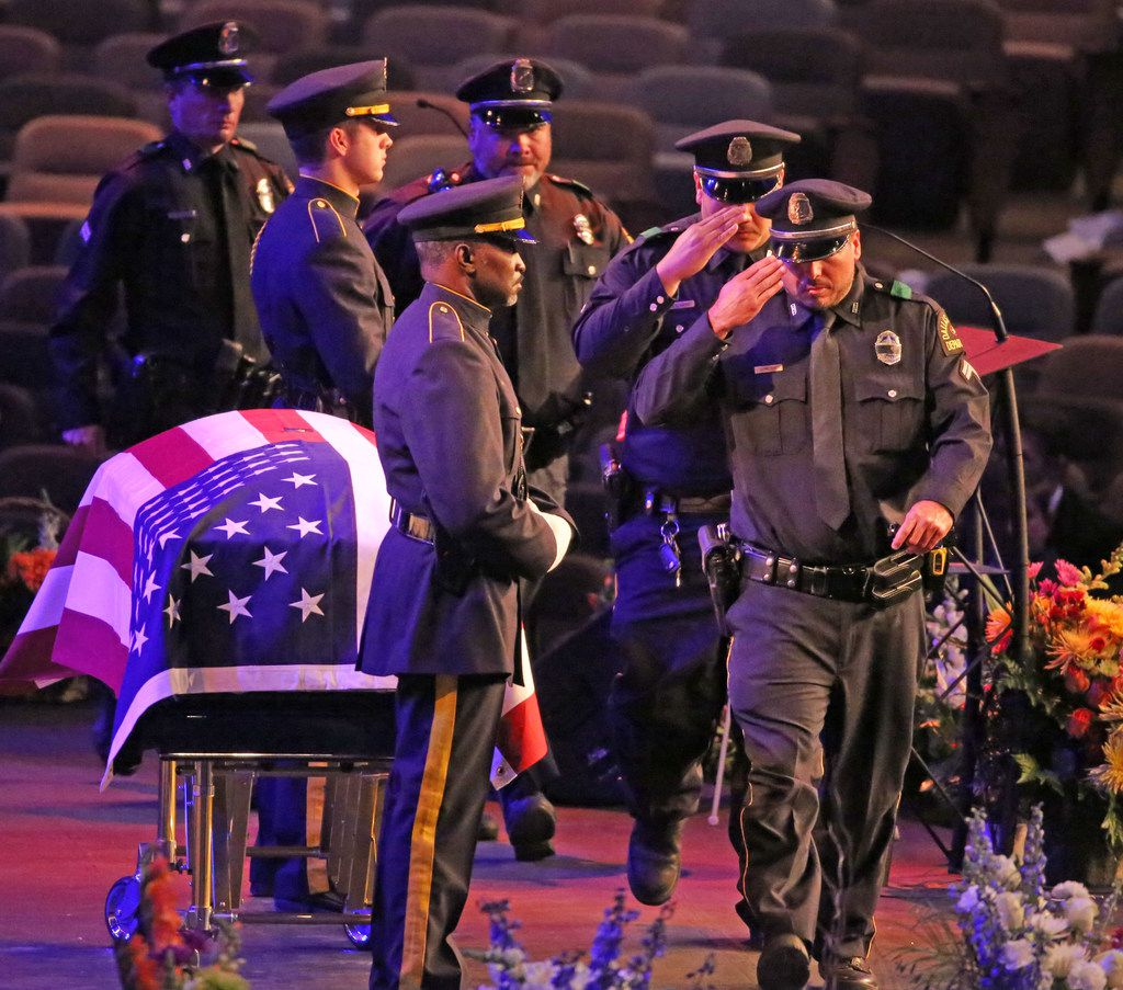 Dallas police officers salute their fallen comrade during the uniformed officers pass-by.
