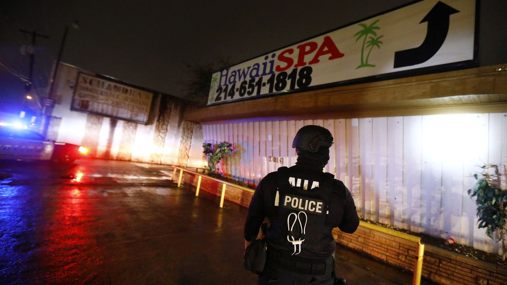 A Dallas Police vice officer inspects the outside of Jade Spa, one of the longest-running illicit massage parlors in Dallas.