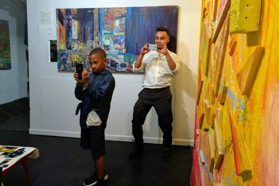 Artist Arjoon KC (right) snaps a photo in his AFactory Studio in Irving.