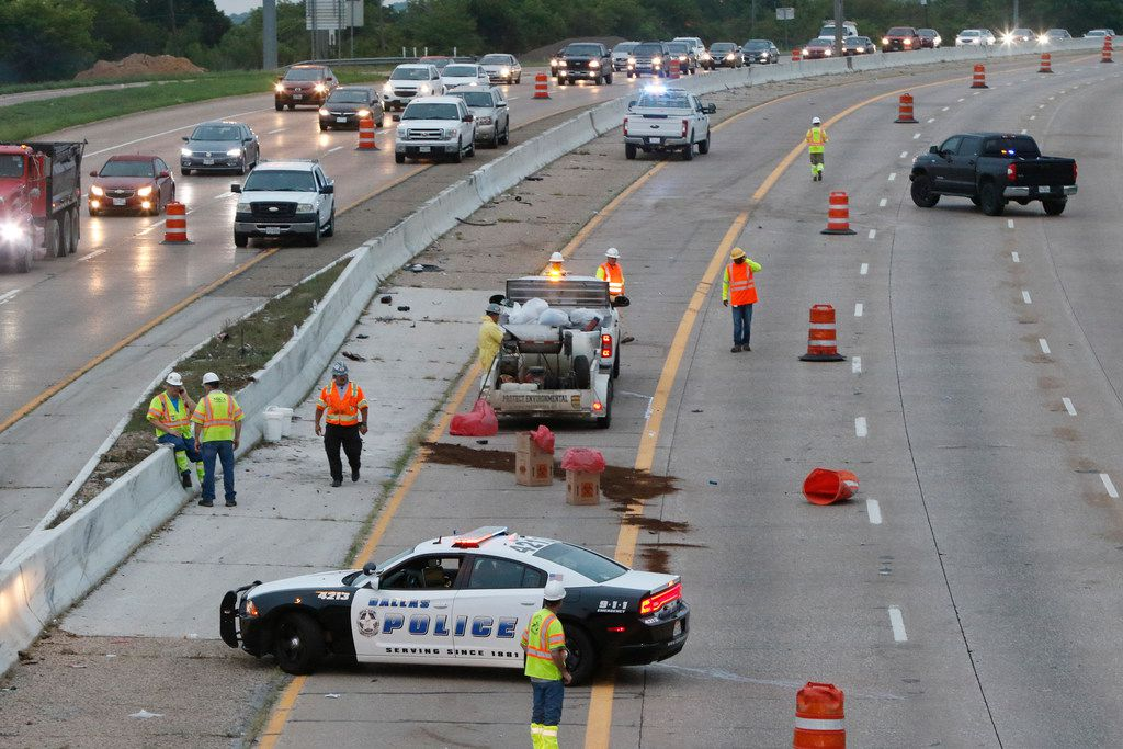 Crews clean up southbound Interstate 35 near the Overton Rd exit early Thursday morning, September 13, 2018 in Dallas. A red pickup drove through orange traffic cones as it headed south on the highway and struck part of a metal sign that was being loaded onto an 18-wheeler with a crane, police said. Part of the sign hit the worker and killed him. The driver of the pickup was not hurt but was taken into custody, police said. (Irwin Thompson/The Dallas Morning New)