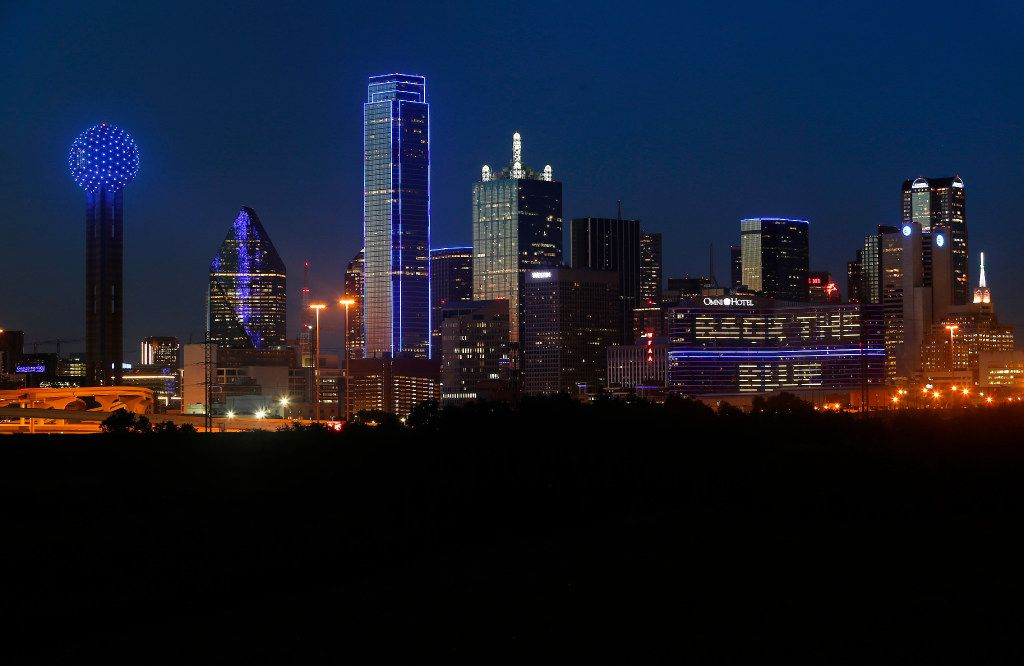 The skyline of Dallas is aglow in blue on July 7, 2017 to remember the four Dallas police officers and one Dallas Area Rapid Transit officer killed in the 2016 police ambush.
