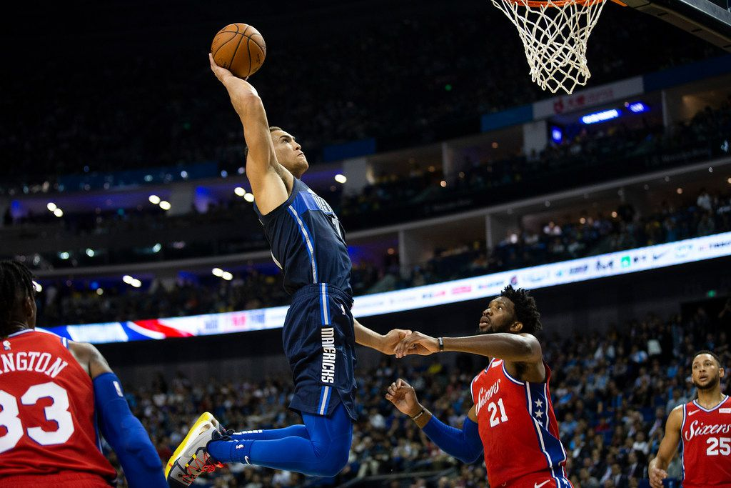 Dallas Mavericks forward Dwight Powell (7) dunks the ball over Philadelphia 76ers forward Joel Embiid (21) during the first half of an NBA China Games 2018 preseason basketball game at Mercedes-Benz Arena on Friday, Oct. 5, 2018, in Shanghai. (Smiley N. Pool/The Dallas Morning News)