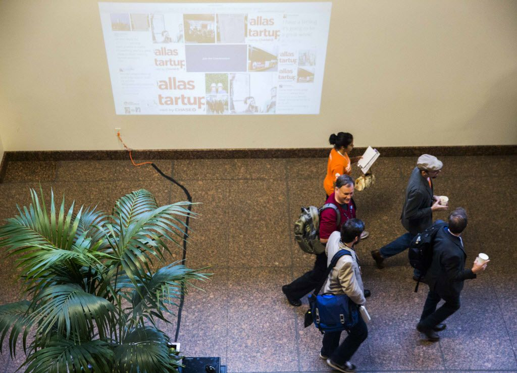 Dallas Startup Week participants walk past a projected social media wall on Tuesday, April 12, 2016 at 1700 Pacific Avenue in downtown Dallas.  (Ashley Landis/The Dallas Morning News)