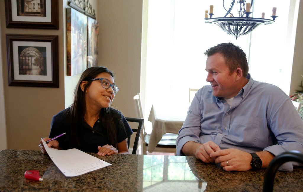 Jason Ballard helps his 12-year-old adoptive daughter, Emi, with math homework at their home in Longview. Emi has DOCK8, a rare genetic disorder that causes immunodeficiency. The Ballards are trying to find a bone marrow donor for her.