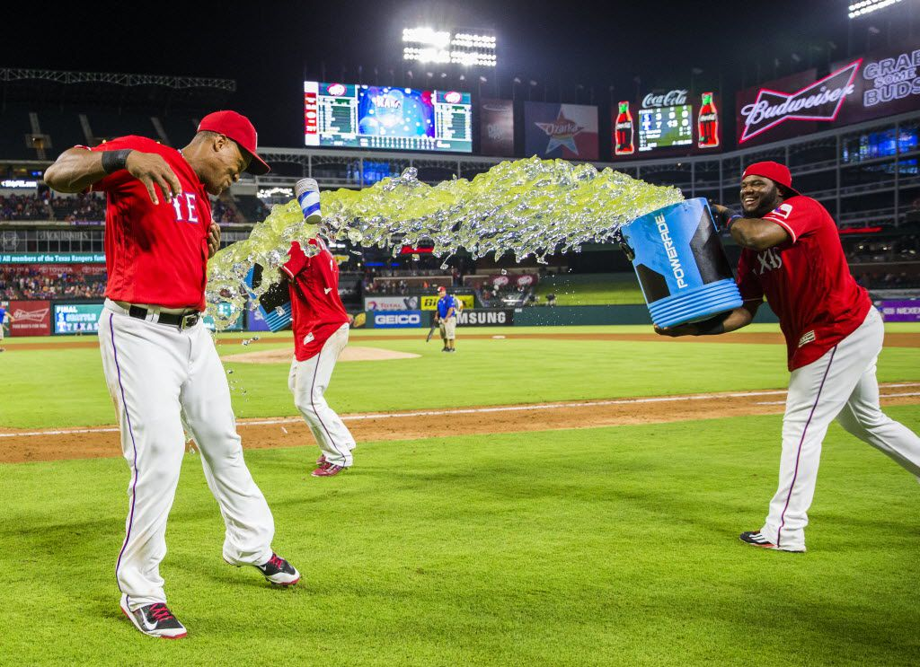 Texas Rangers third baseman Adrian Beltre (29) jumps back from a Gatorade dump by shortstop Elvis Andrus (1) and shortstop Hanser Alberto (2) after a 7-3 win over the Seattle Mariners on Friday, June 3, 2016 at Globe Life Park in Arlington, Texas.  (Ashley Landis/The Dallas Morning News)