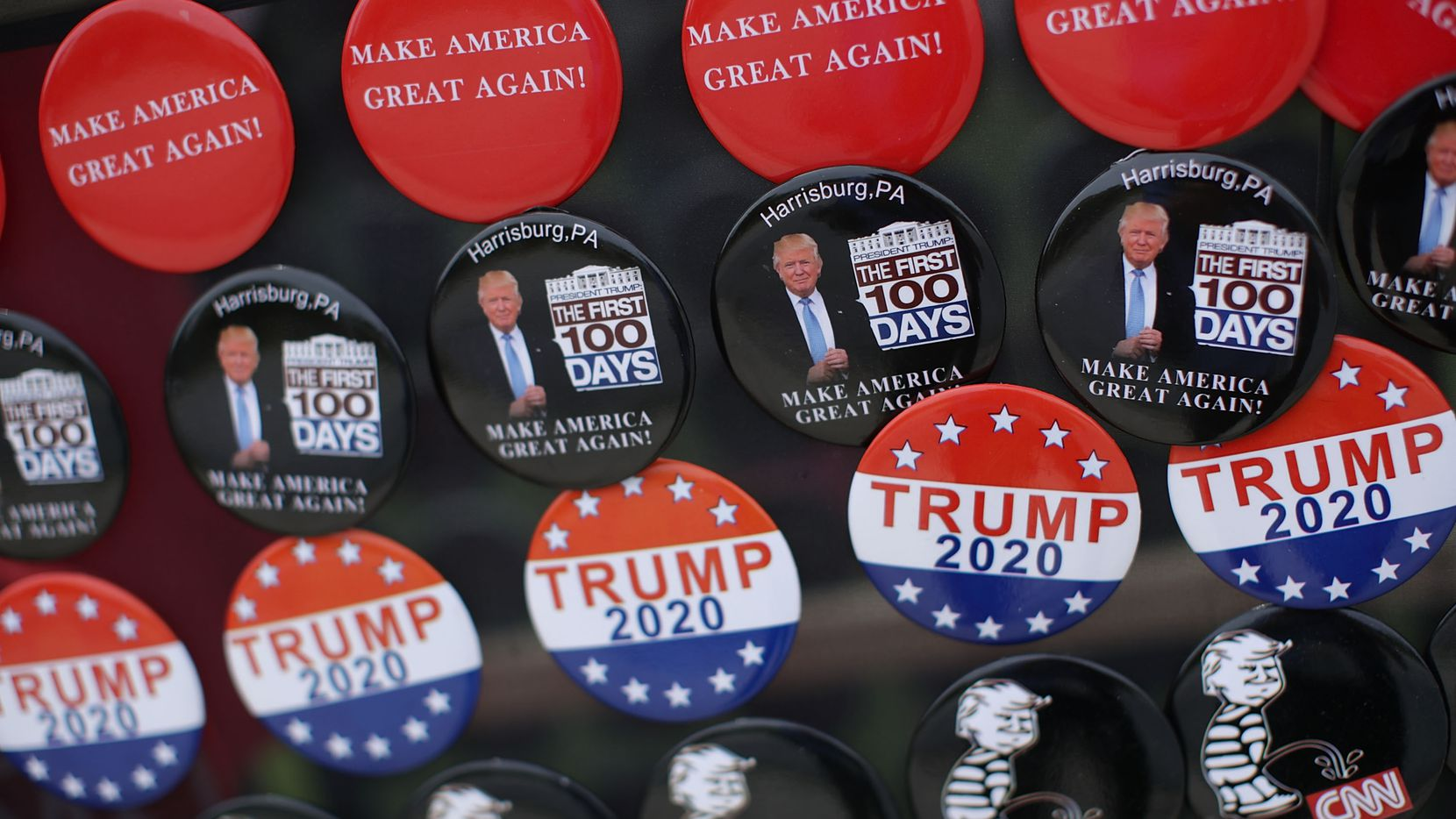 """Political buttons were on display at a street vendor outside the Pennsylvania Farm Show Complex & Expo Center prior to a """"Make America Great Again Rally"""" on April 29, 2017 in Harrisburg, Pa. President Donald Trump is holding a rally to mark his first 100 days of his presidency.  (Alex Wong/Getty Images)"""