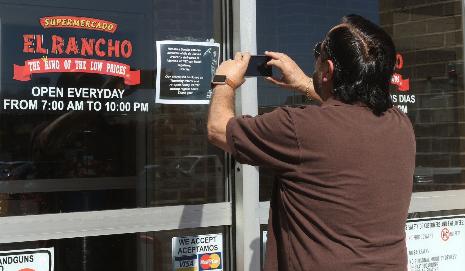 "Edgar Maldonado takes a picture of a sign, in English and Spanish, on the door of Supermercado El Rancho, on Gaston Ave, in Dallas, that informed him that the store was closed on Thursday, Feb. 16, 2017 in support of the ""Day Without Immigrants"" protest."