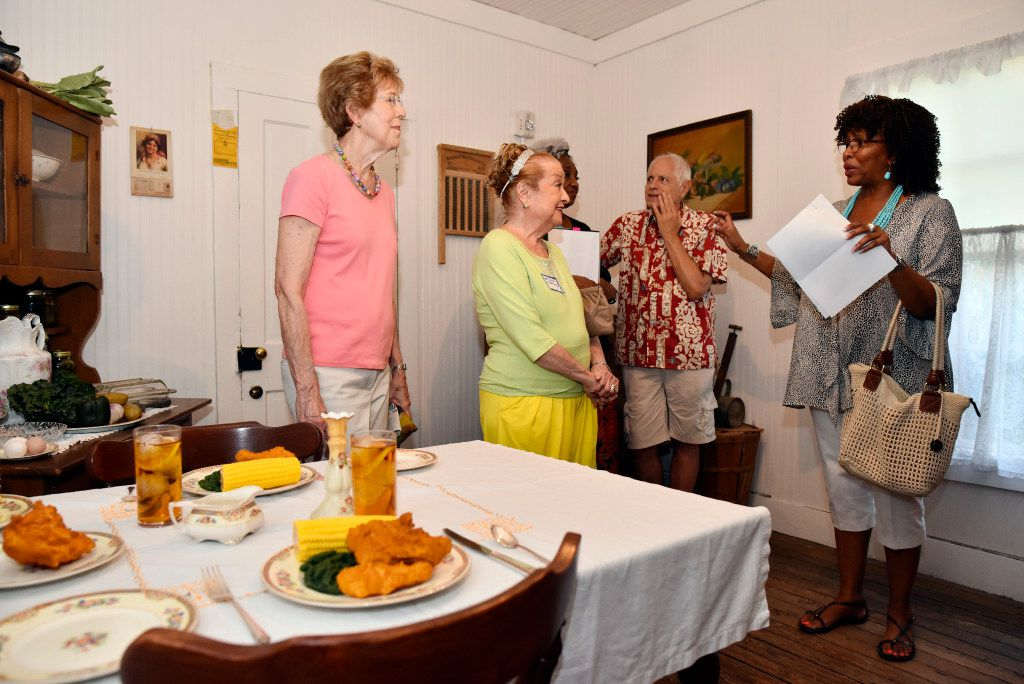 Jonna Shampine, far-left, and Anita N. Martinez, listen to Carole Davis, far-right, of Remembering Black Dallas, as they tour the kitchen inside of a shotgun house during the opening celebration of the new exhibit titled Neighborhoods We Called Home, at the Dallas Heritage Village near downtown Dallas, Thursday, Aug. 31, 2017. The kitchen set pictured is dated from the 1930s. Ben Torres/Special Contributor