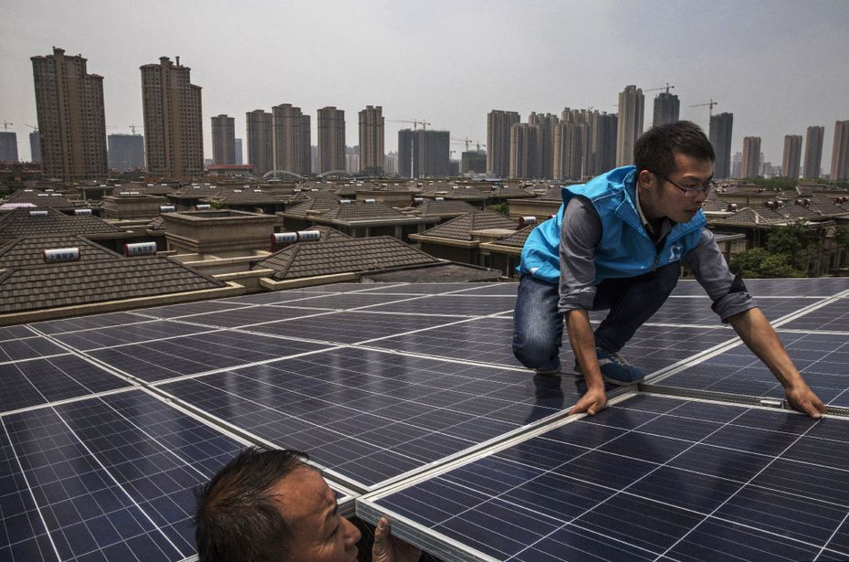Chinese workers from Wuhan Guangsheng Photovoltaic Company install solar panels on the roof of a building.  To ease the country's longtime dependence on coal and other fossil fuels, China's government has made strategic investments in the solar panel industry, which has created intense global competition in the estimated $100 billion global solar energy market.