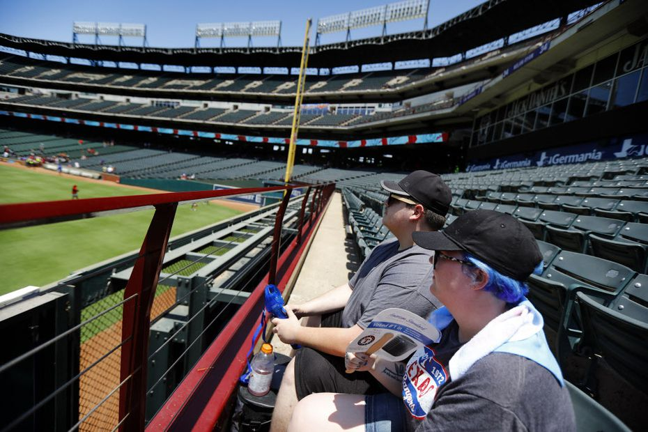 Texas Rangers fans Paige Baucom (front) and Patrick Rovell of Lone Oak try to keep cool before Sunday's game at Globe Life Park in Arlington.