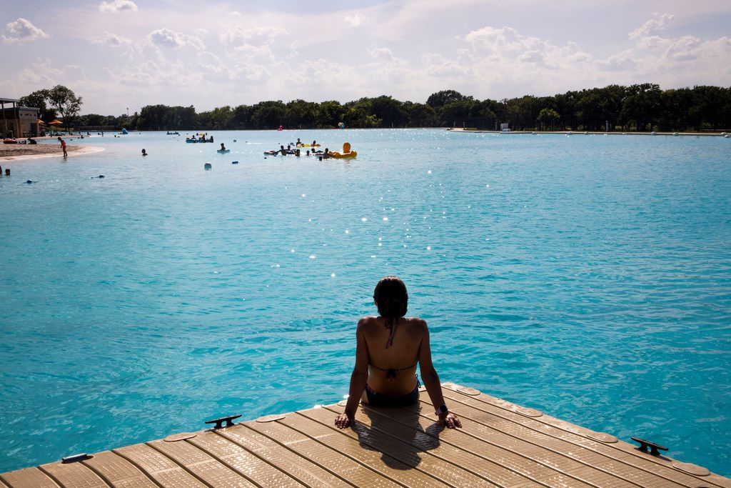 Thirteen-year-old Sachiko Steinhilper sits on one of the docks at the Crystal Lagoon at Windsong Ranch in Prosper on Tuesday.