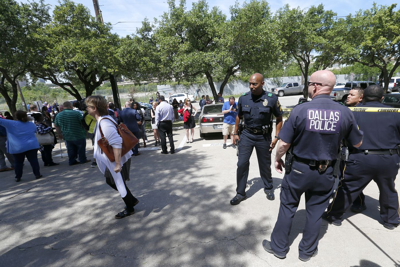 Dallas Police officers talk with workers outside the office building Monday. (Jae S. Lee/Staff Photographer)