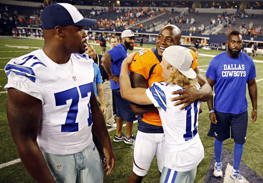 Former Dallas Cowboys player and current Denver Broncos defensive end DeMarcus Ware (94) hugs Dallas Cowboys wide receiver Cole Beasley (11) as tackle Tyron Smith looks on during the second half of Dallas' 27-3 preseason loss Thursday, August 28, 2014 at