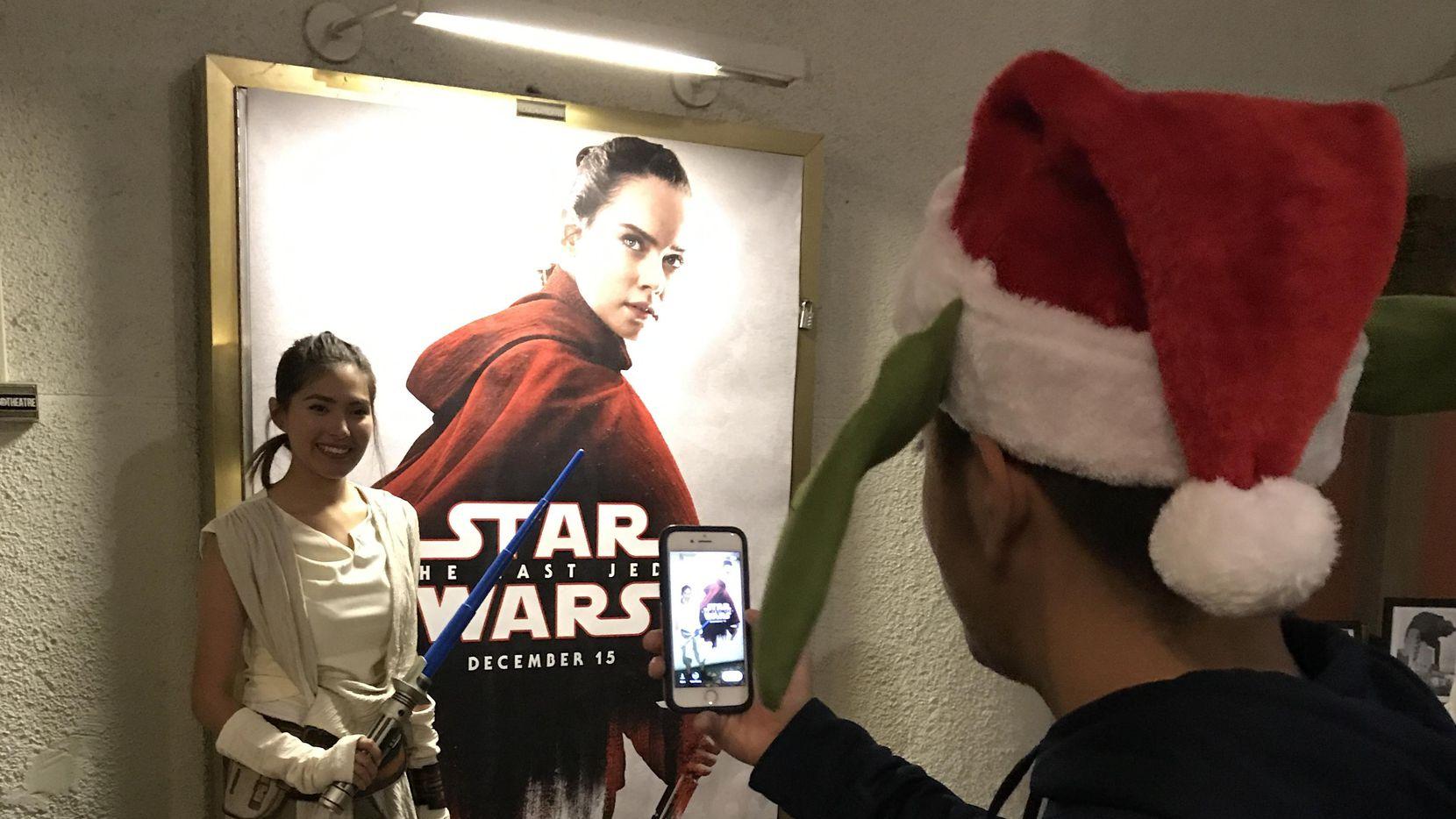 """Javier Ramírez retrata a Stephanie Rodríguez, junto a un poster de Rey, protagonista de """"The Last Jedi"""", el jueves en Texas Theater de Dallas.(JAVIER GIRIBET/ESPECIAL PARA AL DÍA)"""