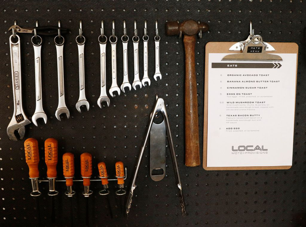 A menu hangs on a tool pegboard at Local Moto + Provisions, a vintage motorcycle repair shop that serves as an extension of Local Press in Dallas. They support local vendors while creating farm to bottle cold-pressed, organic juices served in glass bottles + classic coffee & espresso drinks. Photo taken on Monday, September 25, 2017. (David Woo/The Dallas Morning News)