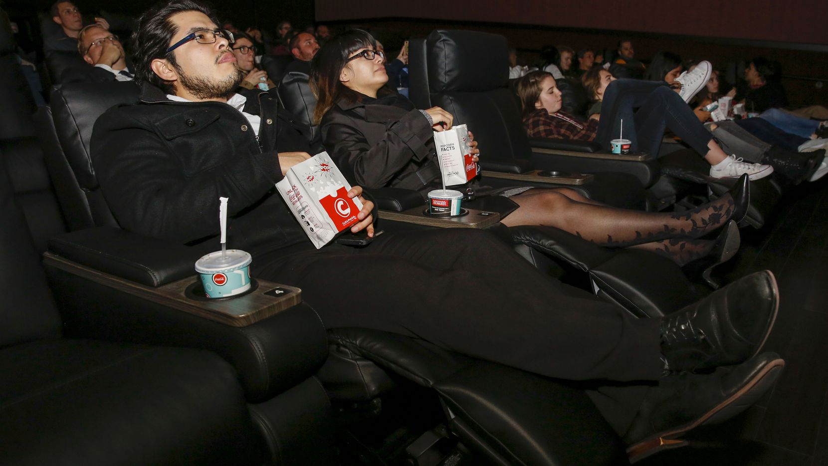 Gustavo Alvarado and Gemma Ortega recline in their seats at a party before the opening of the remodeled Cinemark movie theater in central Plano. For the first time in 25 years, this theater has recliners.