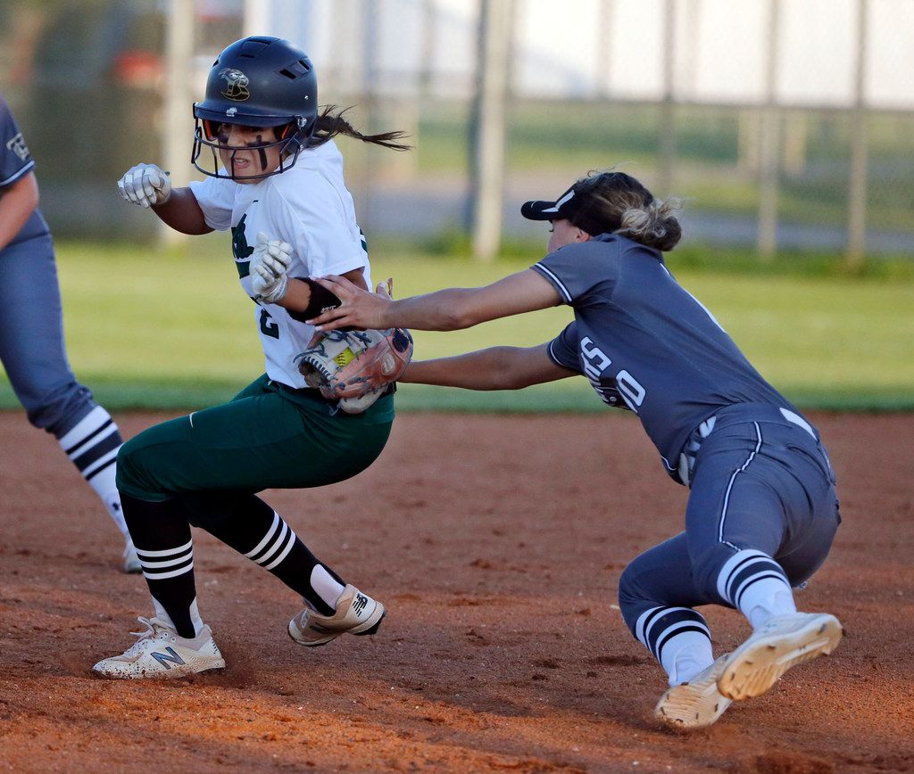 Birdville's Alicia Mora (left) is tagged out in a rundown by The Colony's Jayda Coleman during the first inning of The Colony's 4-1 win Game 2 on Friday. (Michael Ainsworth/Special Contributor)