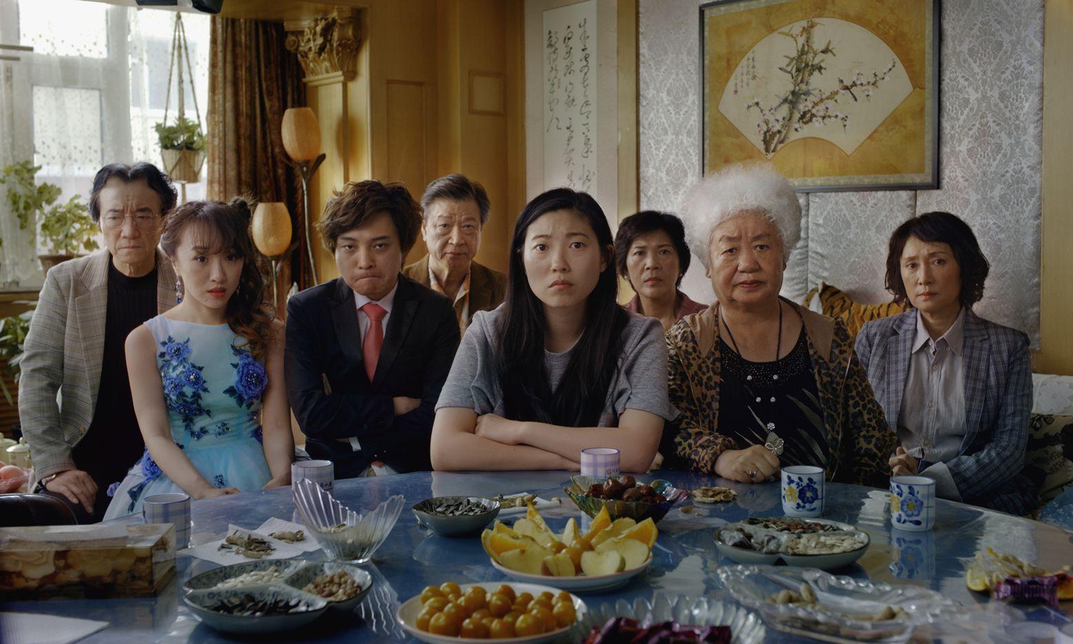 Billi (Awkwafina, center) and her extended family (from left: Jiang Yongbo, Aoi Mizuhara, Chan Han, Tzi Ma, Li Xiang, Lu Hong, Diana Lin) await news at Nai Nai's dining table.
