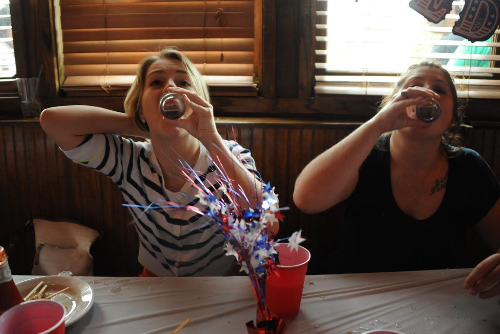 Hallie Levenwood and Lyndsey Luther have a tequila shoot out at the 7th annual Brass Knuckles Corn Dog Beatdown at The Libertine Bar on July 4, 2015.