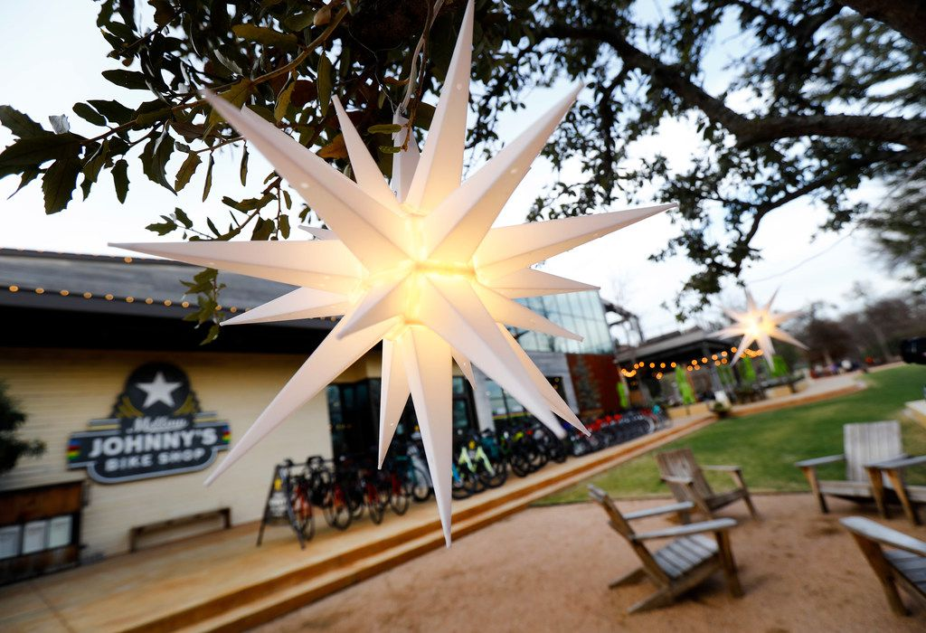 Lighted fixtures adorn trees in a sitting area outside the Mellow Johnny's Bike Shop (left) and Press Cafe (right) at The Trailhead at Clearfork event area in Fort Worth.