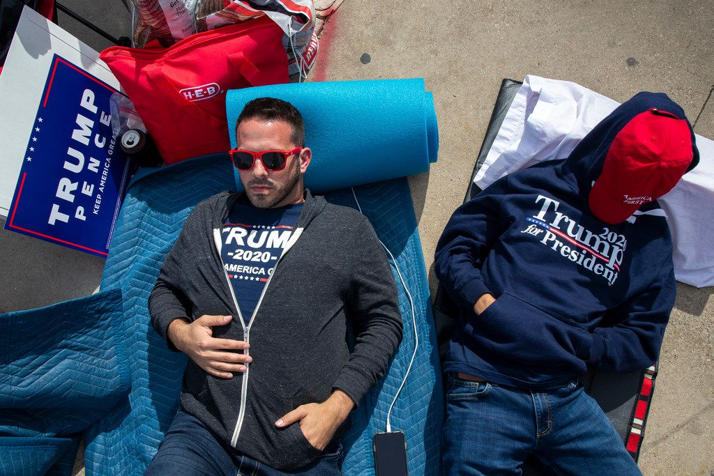 Brandon Stout (left) and his son, Kaden Stout take a brief nap while they camp out in line in front of the American Airlines Center in Dallas on Wednesday, Oct. 16, 2019. President Trump will host a rally at the center on Thursday evening.