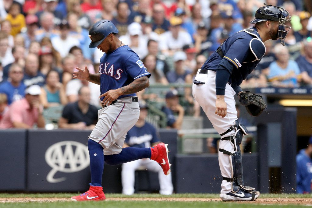 MILWAUKEE, WISCONSIN - AUGUST 11:  Willie Calhoun #5 of the Texas Rangers scores a run past Manny Pina #9 of the Milwaukee Brewers in the seventh inning at Miller Park on August 11, 2019 in Milwaukee, Wisconsin. (Photo by Dylan Buell/Getty Images)